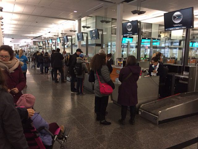 Parents and their children checking in at the Air Transat counters